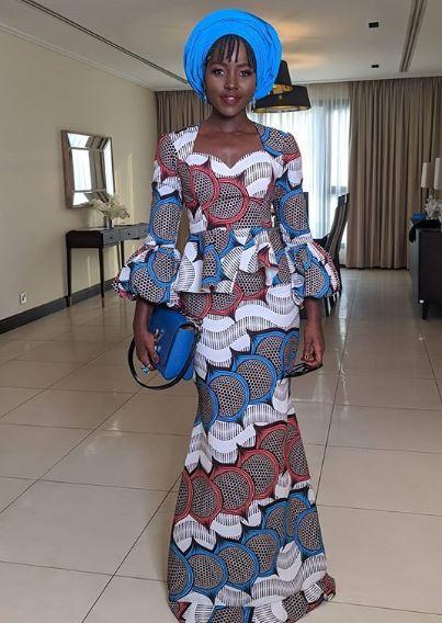 lupita nyongo dans un ensemble en tissu wax, avec une longue jupe en tissu pagne africain