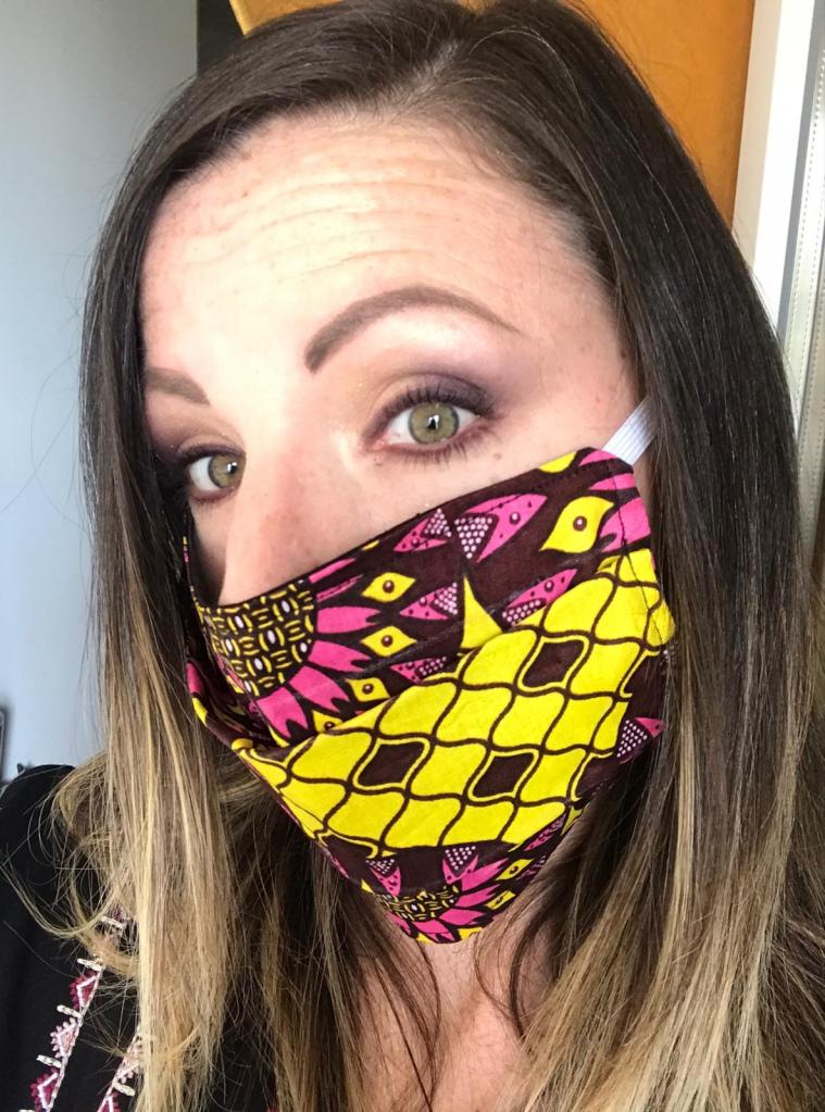 se maquiller les yeux en portant un masque barrière style ethnique en tissu pagne ou tissu wax